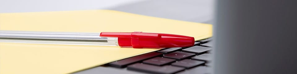 Red pen kept over laptop